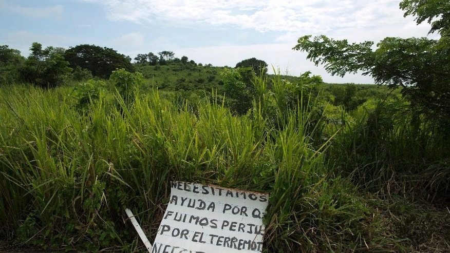 """This April 25, 2016 photo shows a sign that reads in Spanish; """"We need help because we were affected by the earthquake, we need food and medicine,"""" on the side of a highway outside Pedernales, Ecuador. More than a dozen roads were closed due to damage from th April 16, 7.8-magnitude earthquake, making it harder for rescuers to reach where they were needed most. (AP Photo/Rodrigo Abd)"""