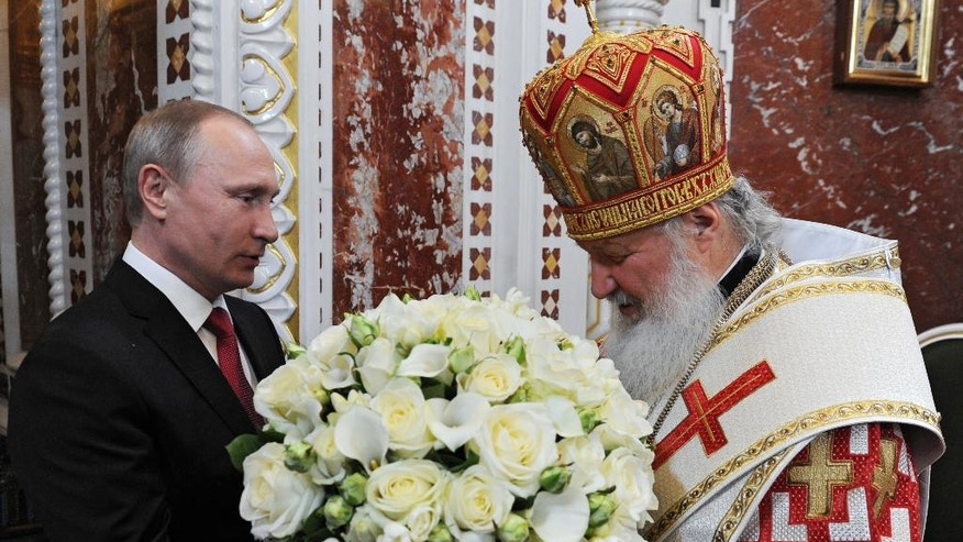 Russian President Vladimir Putin, left, congratulates Russia's Orthodox Church Patriarch Kirill with Easter prior to the Easter service in the Christ the Savior Cathedral in Moscow, Russia, early Sunday, May 1, 2016.(Mikhail Klimentyev/Sputnik, Kremlin Pool Photo via AP)