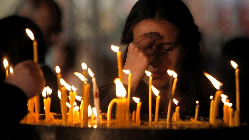 A woman crosses herself after lighting a candle during Easter service at St. Clement Christian Orthodox church in Macedonia's capital Skopje, early Sunday, May 1, 2016. (AP Photo/Boris Grdanoski)
