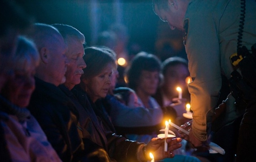 Carl and Marsha Mueller hold candles being lit during a vigil at a candlelight memorial honoring aid worker Kayla Mueller at the Prescott's Courthouse Square in Prescott, Arizona, February 18, 2015. Friends and colleagues of Mueller, the aid worker who died while a captive of militants of the Islamic State group in Syria, remembered her on Saturday in a candlelight vigil as someone who was trying to give back in gratitude for a life of freedom. Mueller, 26, was confirmed to have died under circumstances that remain unclear about 18 months after she was abducted while leaving a hospital in northern Syria. REUTERS/Deanna Dent (UNITED STATES - Tags: POLITICS OBITUARY CIVIL UNREST) - RTR4Q6HP