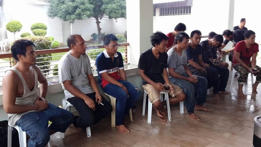 In this photo provided by the Office of Sulu Governor, freed Indonesian tugboat crewmen sit inside a house in Jolo, Sulu province, southern Philippines on Sunday May 1, 2016. Abu Sayyaf militants have freed 10 Indonesian tugboat crewmen who were seized at sea in March and taken to a jungle encampment in the southern Philippines, officials said Sunday. (Office of the Sulu Governor via AP)