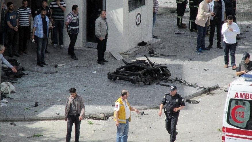 Security and forensic officials and medics investigate around the remains of a car after an explosion outside a police station in Gaziantep, Turkey, Sunday, May 1, 2016. Private NTV television says the explosion appears to have been caused by a car bomb. (IHA agency via AP) TURKEY OUT