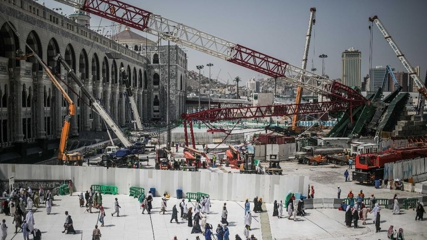 FILE- In this Tuesday, Sept. 15, 2015 file photo, Muslim Pilgrims walk past the site of a crane collapse that killed over a hundred Friday at the Grand Mosque in the holy city of Mecca, Saudi Arabia. Employees at giant construction firm, the Saudi Binladin Group, have set fire to more than seven company buses to protest a reportedly large round of looming layoffs and not being paid their salaries for months. (AP Photo/Mosa'ab Elshamy, File)