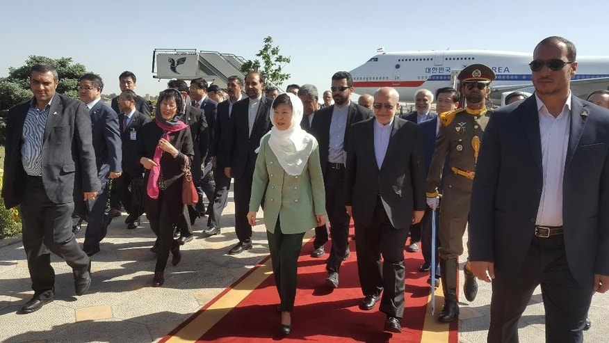 South Korean President Park Geun-hye, with white scarf, arrives at the Mehrabad airport as she is welcomed by Iranian Industry Minister Mohammad Reza Nematzadeh, center right, in Tehran, Iran, Sunday, May 1, 2016. (AP Photo/Vahid Salemi)