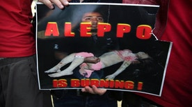 A Syrian man holds a sign during a protest in front of the United Nations headquarters in Beirut, Lebanon, Sunday, May 1, 2016, against Syrian President Bashar Assad's military operations in areas held by insurgents around the country, mostly in the northern city of Aleppo that has been the main point of violence. (AP Photo/Bilal Hussein)