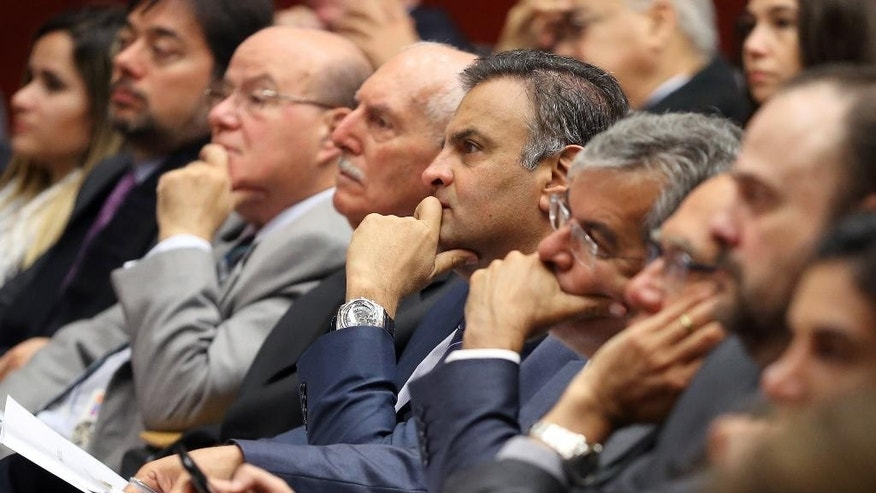 FILE - In this March 31 2016 file photo, Brazilian Senator Aecio Neves, center, listens during at a legal conference in Lisbon, Portugual. Neves, the Brazilian opposition PSDB party's 2014 presidential candidate who narrowly lost to the now-embattled incumbent President Dilma Rousseff, was named among many top officials to be investigated for corruption, authorized by Brazil's attorney general according to Brazilian news reports on Monday, May 2, 2016.  (AP Photo/Armando Franca, File)