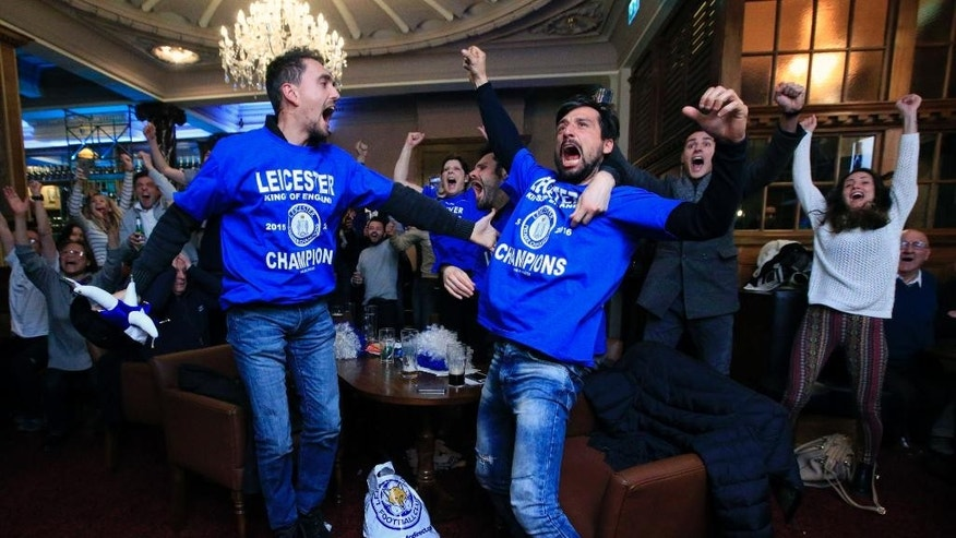 Leicester City fans celebrate in Hogarths public house in Leicester, central England, after Chelsea's Eden Hazard scores the equalising goal against Tottenham Hotspur in their English Premier League soccer match. The match ended 2-2 resulting in Leicester City winning the Premier League, Monday May 2, 2016. (Jonathan Brady/PA via AP)  UNITED KINGDOM OUT
