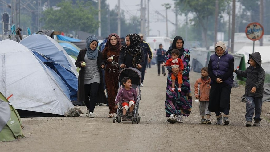 Women and children stroll at a makeshift camp for migrants and refugees at the northern Greek border point of Idomeni, Greece, Monday, May 2, 2016. Many thousands of migrants remain at the Greek border with Macedonia, hoping that the border crossing will reopen, allowing them to move north into central Europe. (AP Photo/Gregorio Borgia)