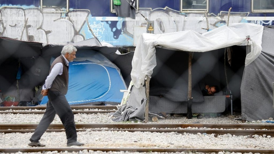 A man lays inside a tent set on the tracks of a train station which was turned into a makeshift camp for migrants and refugees at the northern Greek border point of Idomeni, Greece, Monday, May 2, 2016. Many thousands of migrants remain at the Greek border with Macedonia, hoping that the border crossing will reopen, allowing them to move north into central Europe. (AP Photo/Gregorio Borgia)