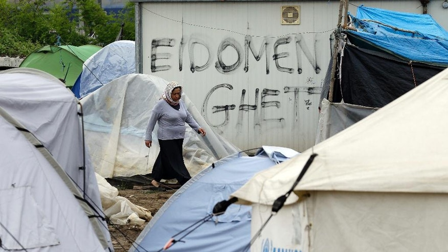 A woman walks past tent and shelters set at a makeshift camp crowded by migrants and refugees at the northern Greek border point of Idomeni, Greece, Sunday, May 1, 2016. Many thousands of migrants remain at the Greek border with Macedonia, hoping that the border crossing will reopen, allowing them to move north into central Europe. (AP Photo/Gregorio Borgia)