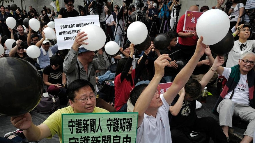 "Protesters try to pierce balloons during a rally outside the Ming Pao's office building in Hong Kong Monday, May 2, 2016. Around 400 people gathered Monday in Hong Kong to protest the dismissal of a veteran editor of the Ming Pao that has triggered concerns about waning press freedoms in the semiautonomous Chinese territory. The Chinese words on placard is read "" To Guard Journalists, To Guard Ming Pao, To Guard Press Freedom"". (AP Photo/Vincent Yu)"