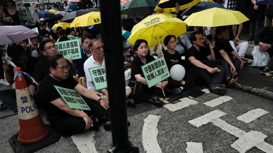 Protesters gather outside the Ming Pao's office building during a rally in Hong Kong Monday, May 2, 2016. Around 400 people gathered Monday in Hong Kong to protest the dismissal of a veteran editor of the Ming Pao that has triggered concerns about waning press freedoms in the semiautonomous Chinese territory. (AP Photo/Vincent Yu)