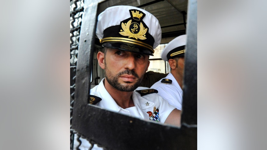 FILE -  In this Friday, May 25, 2012 file photo Italian marine Salvatore Girone, looks out of the window of a vehicle as he is shifted with fellow Marine, Massimiliano Latorre, right, to a different prison in Kochi, India. Italy's Foreign Ministry says Monday, May 2, 2016 an international tribunal in The Hague has decided that Salvatore Girone, an Italian marine being held in India in the shooting deaths of two Indian fishermen mistaken for pirates can return home for the duration of arbitration. (AP Photo, File)