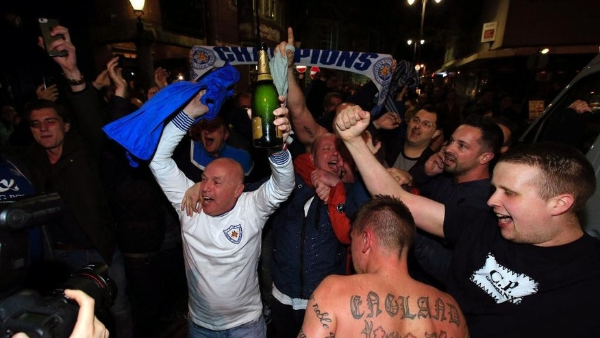 Leicester City fans celebrate in the streets of Leicester after seeing their side crowned English Premier League soccer champions following Tottenham Hotspur's 2-2 draw against Chelsea. The match resulted in Leicester City winning the Premier League, Monday May 2, 2016. (Jonathan Brady/PA via AP)  UNITED KINGDOM OUT