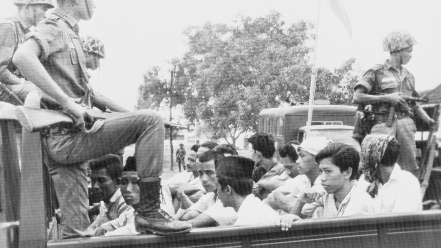 FILE - In this Oct. 30, 1965 file photo, members of the Youth Wing of the Indonesian Communist Party (Pemuda Rakjat) are guarded by soldiers as they are taken by open truck to prison in Jakarta.  Survivors of Indonesia's anti-communist massacres in 1965 have submitted a list of what they say are more than 100 mass graves to the government after the president called for an investigation into the killings. Five survivors, aged in their 70s, who are founders of the Research Foundation for 1965 Murder Victims, gave the documents Monday, May 2, 2016,  to the Coordinating Ministry for Politics, Legal and Security Affairs. (AP Photo/File)