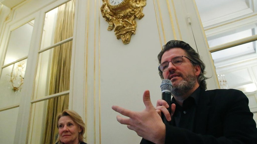 Danish artist Olafur Eliasson, right, gestures during a media conference in Paris, France, Monday, May 2, 2016. Artist Elafur Oliasson vows to turn visitors into explorers in his next summer project at the palace of Versailles. President of the Public Establishment of the Palace, Museum and National Estate of Versailles Catherine Pegard, is on the left.(AP Photo/Michel Euler)