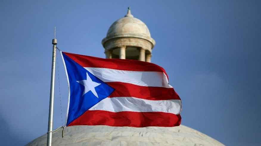 FILE - In this Wednesday, July 29, file 2015 photo, the Puerto Rican flag flies in front of Puerto Rico's Capitol as in San Juan, Puerto Rico. Puerto Rico Gov. Alejandro Javier Garcia Padilla said on Sunday, May 1, 2016, that negotiators for the U.S. territory's government have failed to reach a last-minute deal to avoid a third default and that he has issued an executive order to withhold payment. (AP Photo/Ricardo Arduengo, File)
