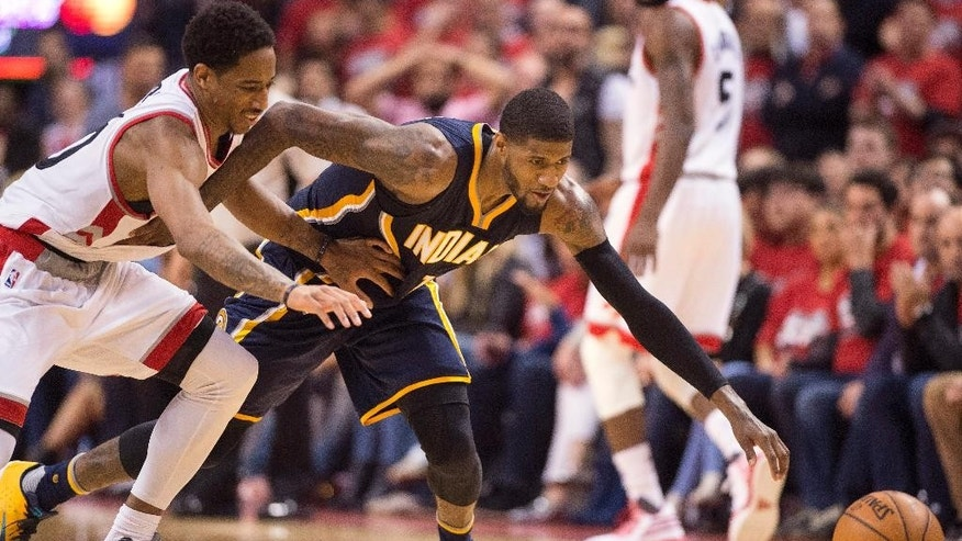 Indiana Pacers forward Paul George and Toronto Raptors guard DeMar DeRozan battle for a loose ball during second half round one NBA playoff basketball action in Toronto on Sunday, May 1, 2016. (Frank Gunn/The Canadian Press via AP)