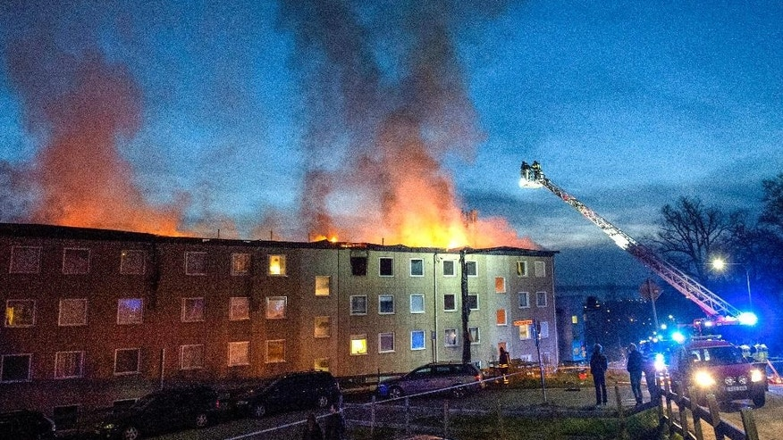 Firemen fight to contain a blaze at an apartment building in  in Huskvarna, southern Sweden, late Monday May 1, 2016. Swedish rescue workers said that the apartment building fire forced the evacuation of more than 150 people when the blaze raged on the top floor, spreading from end to end along the 60-meter (200-foot) long building. ( Anna Hallams / TT via AP) SWEDEN OUT