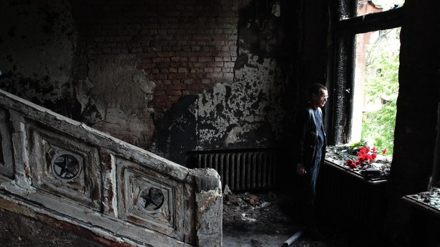 FILE - In this Sunday May 4, 2014 file photo, a man lays flowers inside the burnt trade union building in Odessa, Ukraine. Demonstrators have gathered in the Ukrainian city of Odessa to mark the second anniversary of the street clashes that culminated in a fire that killed 43 people as they took shelter from opponents.  (AP Photo/Sergei Poliakov)