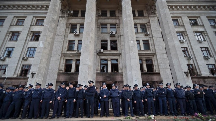 FILE - In this Saturday, May 3, 2014 file photo, police troops guard the burnt out trade union building in Odessa, Ukraine. Demonstrators have gathered in the Ukrainian city of Odessa to mark the second anniversary of the street clashes that culminated in a fire that killed 43 people as they took shelter from opponents. (AP Photo/Vadim Ghirda, File)