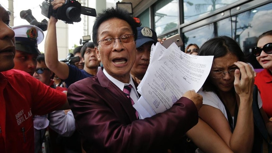 Salvador Panelo, lawyer of presidential candidate Rodrigo Duterte, gestures as he holds documents before meeting Philippine senator and vice-presidential candidate Antonio Trillanes IV at a bank in Pasig, east of Manila, Philippines on Monday, May 2, 2016. Allegations that the Philippine presidential frontrunner kept a fat bank account which was not publicly declared as required by law have not been resolved as hoped for after Trillanes faced Duterte's lawyer at the bank. (AP Photo/Aaron Favila)