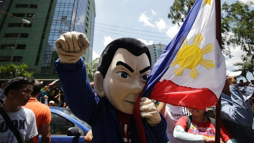 A mascot of presidential candidate Rodrigo Duterte kisses the Philippine flag as he joins supporters outside a bank in Pasig, east of Manila, Philippines on Monday, May 2, 2016. Allegations that the Philippine presidential frontrunner kept a fat bank account which was not publicly declared as required by law have not been resolved as hoped for after his accuser faced Duterte's lawyer at the bank. (AP Photo/Aaron Favila)