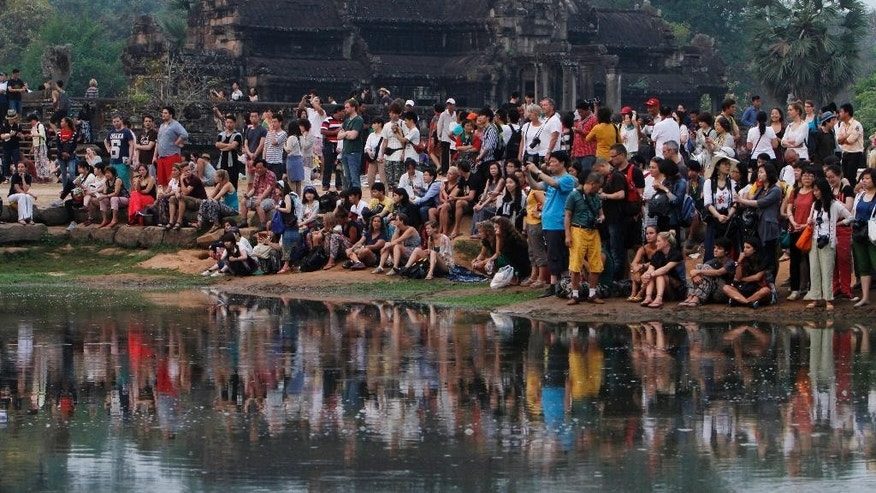FILE - In this March 20, 2015 file photo, tourists wait for sunrise at the Angkor Wat temples outside Siem Reap, Cambodia. The main road alongside Cambodia's famed Angkor Wat temple is now off-limits to cars as authorities seek to ease traffic jams at the site that draws 2.1 million tourists a year. The volume of cars driving near the temple has increased so dramatically in recent years it raised concerns that vibrations caused by the vehicles could harm the temples, built between the 9th and 15th centuries. (AP Photo/Heng Sinith,File)