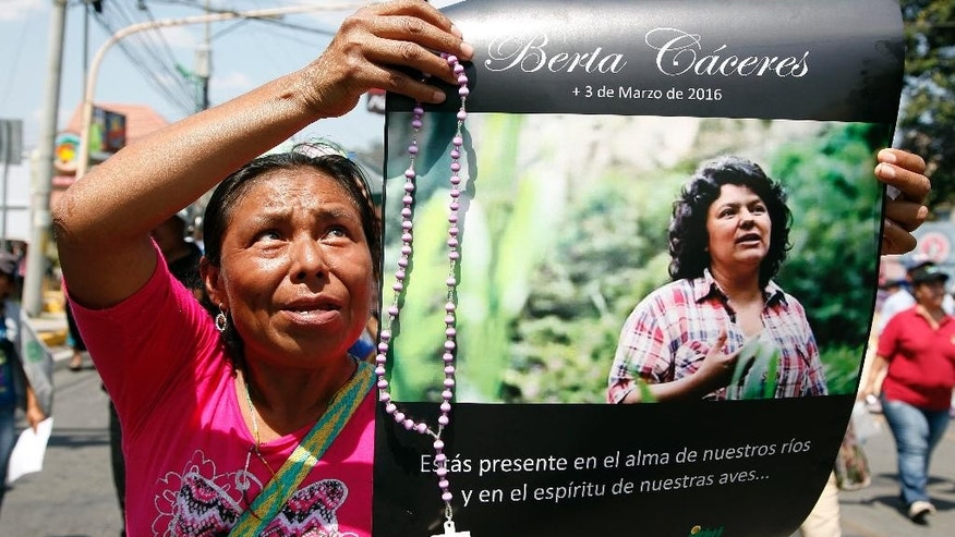 FILE - In this March 16, 2016 file photo, a woman holds up a poster with a photo of slain environmental leader Berta Caceres during a protest in Tegucigalpa, Honduras. Caceres reported receiving threats from DESA security personnel, as well as an attempt by a company official to bribe her to call off the demonstrations, according to Billy Kyte, a senior campaigner on land and environmental defense at London-based Global Witness. DESA, or Desarrollos Energeticos SA, is the company carrying out the Agua Zarca hydroelectric project that Caceres lead protests against. (AP Photo/Fernando Antonio, File)