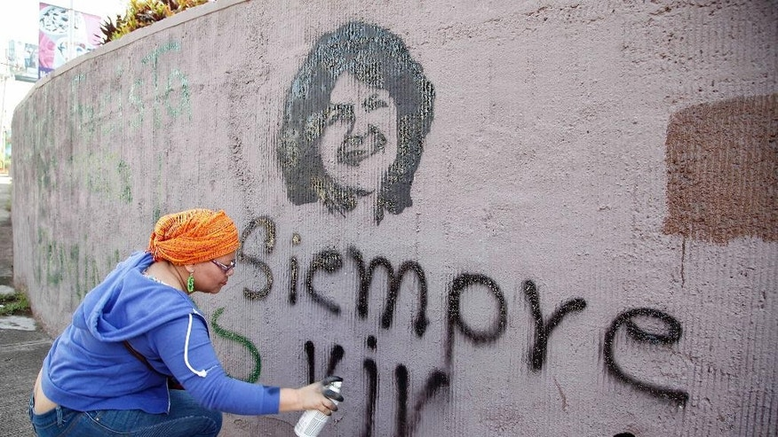 "FILE - In this March 8, 2016 file photo, a woman spray paints the phrase ""Always alive"" below a stenciled image of slain environmental activist Berta Caceres during the commemoration of International Women's Day in Tegucigalpa, Honduras. For months before her death, Caceres complained of regular threats warning her to stop leading protests opposing a hydroelectric project on her Lenca people's ancestral lands. On March 3, armed men forced their way into Caceres' home in the middle of the night, and shot her four times. (AP Photo/Fernando Antonio, File)"