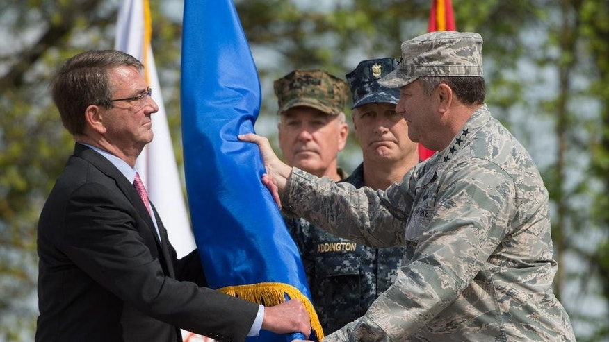 US Secretary of Defense Ashton Carter, left, receives the rank pennant from US Air Force General Philip Breedlove, the outgoing commanding officer of US and NATO troops in Europe, during the change in command at the United States European Command (EUCOM), in Stuttgart, Germany, Tuesday, May 3, 2016, with General Joseph Dunford, second from left, and Command Master Chief Crispian Addington, second from right,  pictured in the background. (Marijan Murat/dpa via AP)