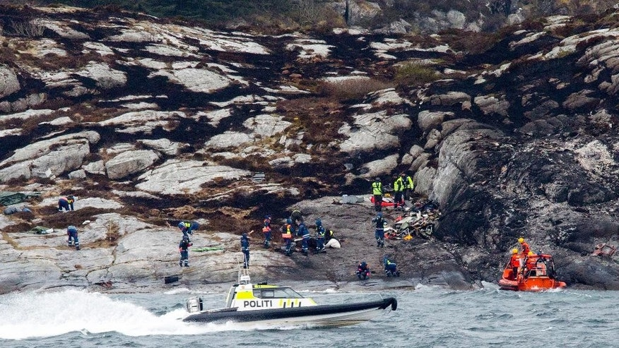 Police and rescue workers investigate at the scene following the Friday April 29 helicopter crash on the coast of Norway near Bergen, Sunday May 1, 2016.  Emergency crews salvaged the wrecked fuselage of the Airbus helicopter from the sea Saturday, along with the flight recorders, and retrieved the rotor blades following the crash which killed the 13 people on board. (Torstein Boe / NTB Scanpix via AP) NORWAY OUT