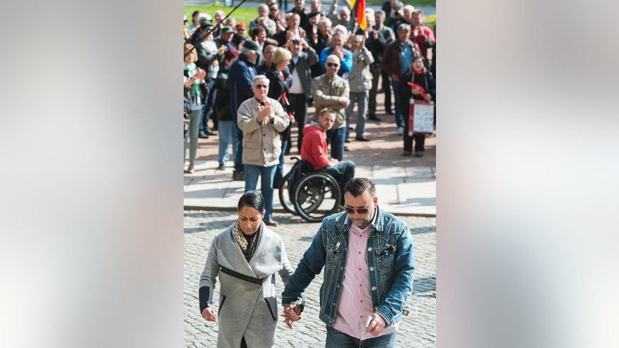 Lutz Bachmann, co-founder of Germany's PEGIDA movement, right, walks together with his wife Vicky Bachmann, left, in front of his supporters prior the beginning of his trial on accusations of incitement in Dresden, eastern Germany, Tuesday, May 3, 2016. (AP Photo/Jens Meyer)
