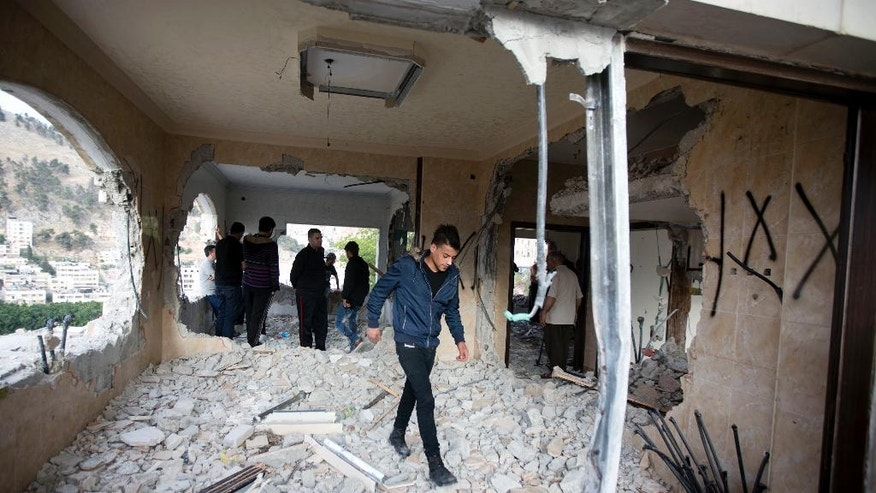Palestinians inspect the damaged house of Zaid Amer, after it was demolished by the Israeli army, in the West Bank city of Nablus, Tuesday, May 3, 2016. The Israeli army demolished the house of Amer, an arrested member of a Hamas cell who carried out an attack and shot dead a U.S. couple, residents of the West Bank Israeli settlement of Neria, while driving home last October, the army said. (AP Photo/Majdi Mohammed)