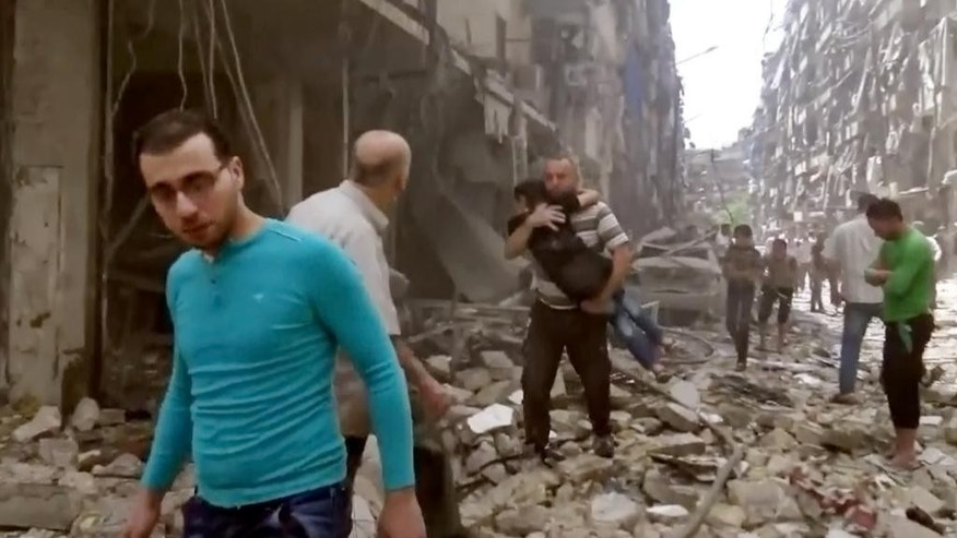 FILE - In this Thursday, April 28, 2016 image made from video and posted online from Validated UGC, a man carries a child after airstrikes hit Aleppo, Syria. Syrian state TV on Tuesday, May 3, 2016 says dozens of people have been killed or wounded when rebels fired rockets into a government-held neighborhood of the northern city of Aleppo. The TV says one of the rockets fired on Tuesday hit the Dubeet hospital in the central neighborhood of Muhafaza. The TV did not give a breakdown of the casualties. (Validated UGC via AP video, File)