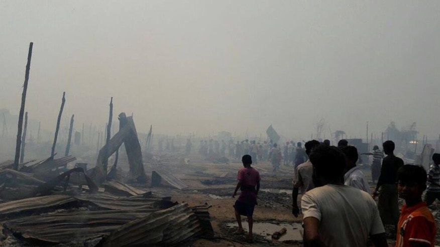 People gather around the remains of Baw Du Pa camp, a camp for stateless Rohingya people in north of Sittwe, western Rakhine state, Myanmar, Tuesday, May 3, 2016. A fire on Tuesday burned down a camp in western Myanmar that shelters members of the country's persecuted Rohingya minority, leaving 440 families homeless. (Photo via AP)