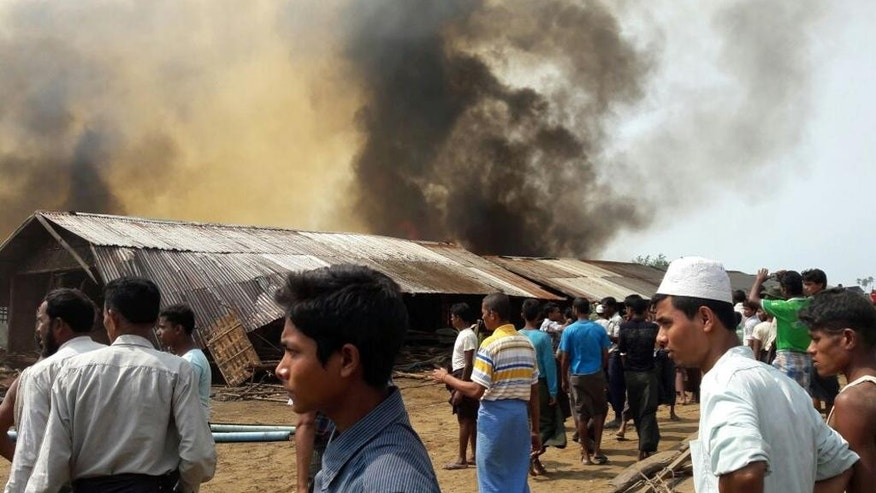 People gather around Baw Du Pa camp, a camp for stateless Rohingya people in north of Sittwe, western Rakhine state, Myanmar, Tuesday, May 3, 2016. A fire on Tuesday burned down a camp in western Myanmar that shelters members of the country's persecuted Rohingya minority, leaving 440 families homeless. (Photo via AP)