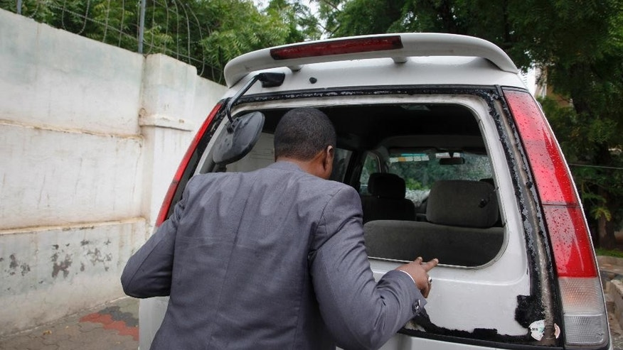 Abdiqadir Dulyar, director for the Somali television station Horn Cable, looks at the smashed window of a car that was carrying journalists working for his station, that unidentified gunmen opened fire on last week although no one was hurt, in Mogadishu, Somalia Tuesday, May 3, 2016. Somali journalists frequently receive threats and although many have been killed, police rarely investigate or provide adequate protection to reporters, according to Human Rights Watch, which marked World Press Freedom Day Tuesday by issuing a report on the dangers faced by Somali journalists. (AP Photo/Farah Abdi Warsameh)