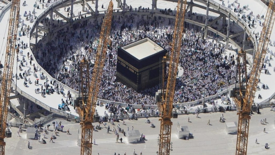 FILE - In this Wednesday, Oct. 16, 2013 file photo, cranes rise at the site of an expansion to the Grand Mosque as Muslim pilgrims circle counterclockwise around the Kaaba at the Grand Mosque in Mecca, Saudi Arabia. Employees at giant construction firm, the Saudi Binladin Group, have set fire to more than seven company buses to protest a reportedly large round of looming layoffs and not being paid their salaries for months. (AP Photo/Amr Nabil, File)