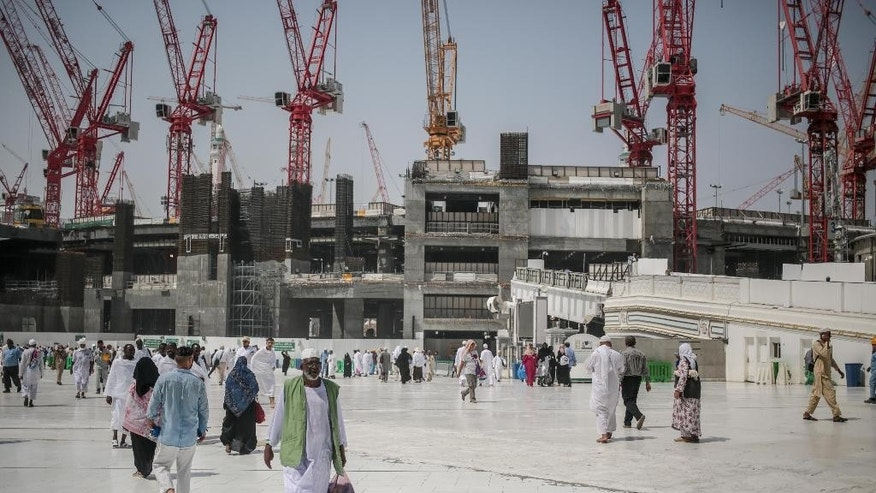 FILE- In this Tuesday, Sept. 15, 2015 file photo, Muslim pilgrims walk outside the Grand Mosque in the holy city of Mecca, Saudi Arabia. Employees at giant construction firm, the Saudi Binladin Group, have set fire to more than seven company buses to protest a reportedly large round of looming layoffs and not being paid their salaries for months. (AP Photo/Mosa'ab Elshamy, File)