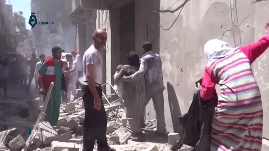 FILE - This Friday, April 29, 2016 image made from video released by Qasion News Agency, a media opposition platform that relies on a network of activists on the ground, shows people scrambling through rubble following airstrikes in Aleppo, Syria. Syrian state TV on Tuesday, May 3, 2016  says dozens of people have been killed or wounded when rebels fired rockets into a government-held neighborhood of the northern city of Aleppo. The TV says one of the rockets fired on Tuesday hit the Dubeet hospital in the central neighborhood of Muhafaza. The TV did not give a breakdown of the casualties. (Qasion News Agency via AP, File)