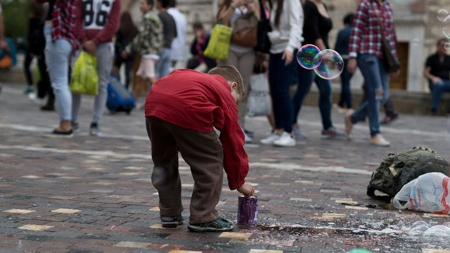 A boy puts coins in a tin, bearing the design of a 500-euro bank note, for a performer creating soap bubbles in Monastiraki Square, central Athens, on Wednesday, May 4, 2016. The 500-euro bill is being discontinued after criticism that the banknote had become a handy aid to money laundering.The European Central Bank's 25-member governing council made the decision at a meeting Wednesday. (AP Photo/Petros Giannakouris)
