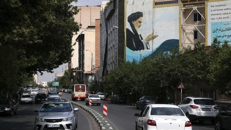 "In this picture taken on Tuesday, July 7, 2015, cars drive past a painting of late Iranian revolutionary founder Ayatollah Khomeini at Bahonar street in northern Tehran, Iran. Chevrolet, the U.S. car brand once advertised as the ""Heartbeat of America,"" won't be rolling new models through the streets of Iran anytime soon despite the recent lifting of sanctions under a nuclear deal with world powers. (AP Photo/Vahid Salemi)"