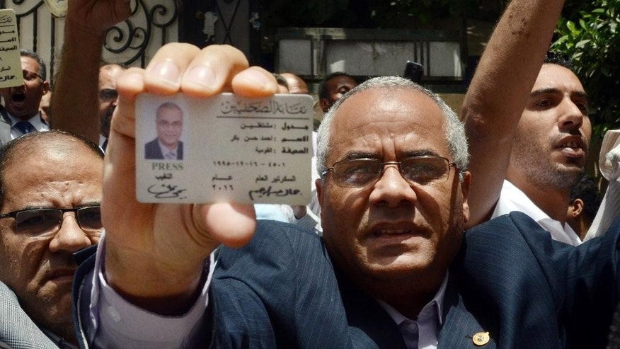 Egyptian American journalist Ahmed Bakr shows his identification card as he and others are blocked from entering a protest near the Press Syndicate in Cairo, Egypt, Wednesday, May 4, 2016. Egyptian riot police cordoned off the headquarters of the journalists' union and limited access to the building Wednesday in an escalating standoff following a raid on the premises and the arrest of two journalists. (AP Photo/Brian Rohan)