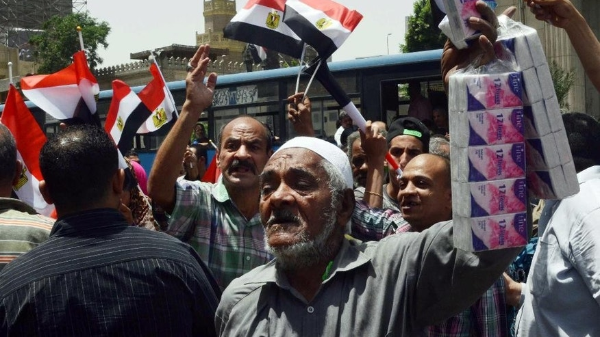 Supporters of Egypt's President Abdel-Fattah el-Sissi demonstrate against a journalists' protest, held at the Press Syndicate, in Cairo, Egypt, Wednesday, May 4, 2016. Egyptian riot police cordoned off the headquarters of the journalists' union and limited access to the building Wednesday in an escalating standoff following a raid on the premises and the arrest of two journalists. (AP Photo/Brian Rohan)