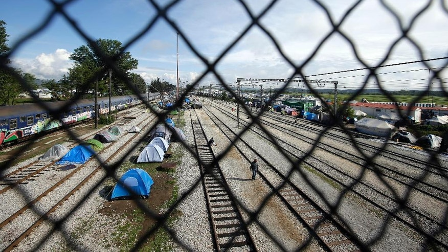 Tents set on the tracks of a train station are framed by a fence at the Greek northern point of Idomeni, Greece, Tuesday, May 3, 2016. Many thousands of migrants remain at the Greek border with Macedonia, hoping that the border crossing will reopen, allowing them to move north into central Europe. (AP Photo/Gregorio Borgia)
