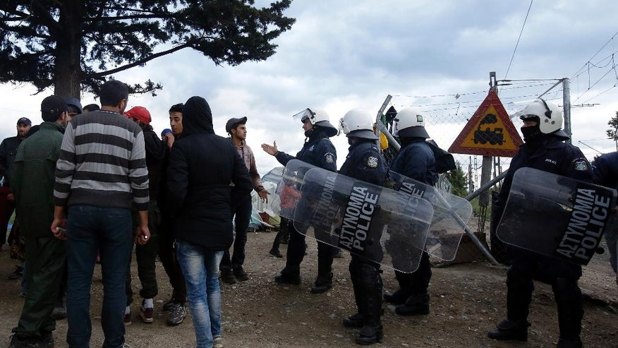 Greek police in riot gear stand near refugees and migrants at the northern Greek border point of Idomeni, Greece, Tuesday, May 3, 2016. Germany and some other EU countries are planning to ask the European Commission for an extension of border controls within the Schengen passport-free travel zone for another six months because they fear a new wave of migrants. (AP Photo/Gregorio Borgia)