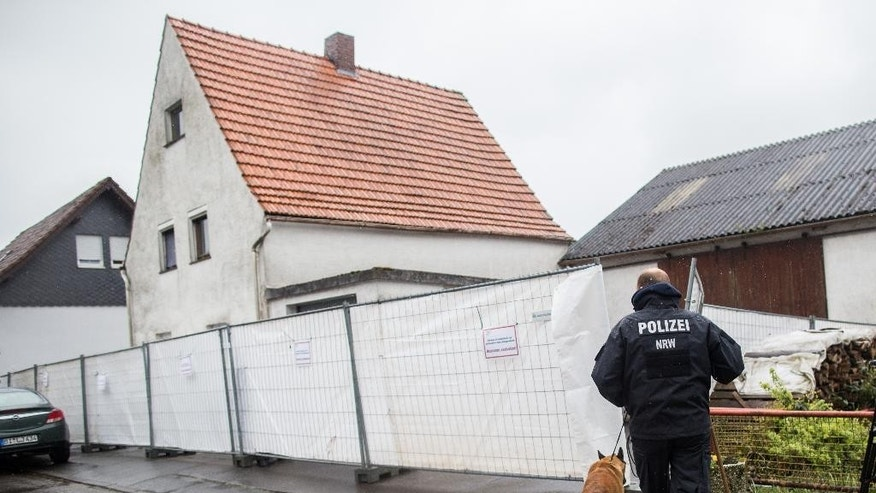 A police officer with a dog passes by a house outside Hoexter, western Germany, Tuesday, May 3, 2016. German authorities said a couple in custody for allegedly holding a woman captive for nearly two months and abusing her so badly that she died are believed also to have killed a second woman. Authorities are investigating whether the pair abused others at their home. (Marcel Kusch/dpa via AP)
