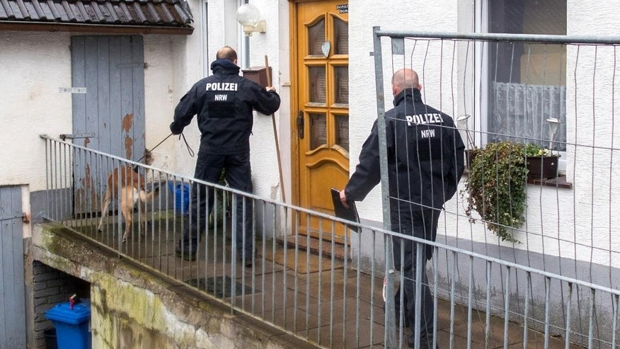 A member of the German police with a dog stands in front of the house of a murder suspect couple in Hoexter, Germany, Tuesday, May 3, 2016.  German authorities said a couple in custody for allegedly holding a woman captive for nearly two months and abusing her so badly that she died are believed also to have killed a second woman. Authorities are investigating whether the pair abused others at their home. (Marcel Kusch/dpa via AP)