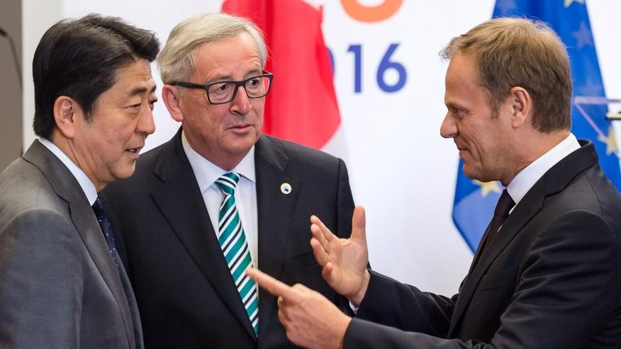 European Council President Donald Tusk, right, and European Commission President Jean-Claude Juncker, center, welcome Japan's Prime Minister Shinzo Abe upon his arrival for an EU Japan leaders' meeting at the EU Council building in Brussels on Tuesday May 3, 2016. (AP Photo/Geert Vanden Wijngaert)